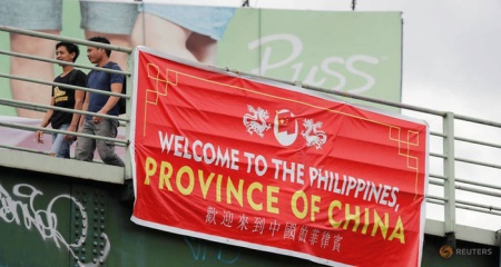 residents-walk-past-a-banner-reading-quot-welcome-to-the-philippines-province-of-china-quot-on-an-overpass-along-the-c5-road-intersection-in-taguig-metro-manila-1-15313803753731011174558